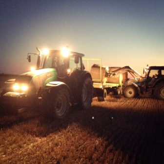 Agrárna ekonomika, agrárna politika - dva traktory na poli nakladajú balíky slamy na vlečku za traktor
